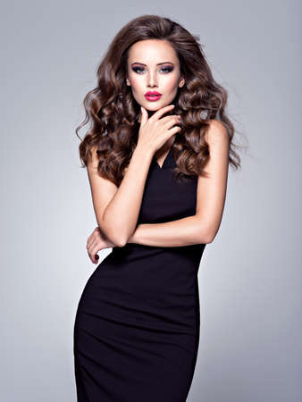 Full portrait of the beautiful woman with long brown curly hair with a slim perfect body, posing at studio over dark background