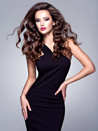 Full portrait of the beautiful woman with long brown curly hair with a slim perfect body, posing at studio over dark background Фото со стока