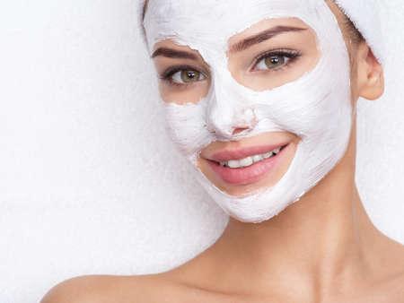 Erwachsene Frau, die sich im Spa-Salon mit kosmetischer Maske im Gesicht entspannt. Schönheitsbehandlung