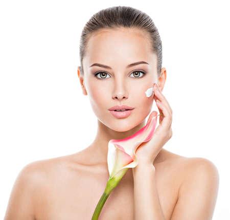Donna che applica crema cosmetica su un viso. Fiore fresco sul corpo