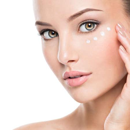 Retrato de mujer con rostro sano aplicando crema cosmética debajo de los ojos Foto de archivo
