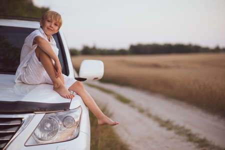 Cute boy 8 years old in white clothes sitting on the hood of a car in nature. Portrait of a smiling child in nature. Blond boy with a cute smile looks at the camera sitting on a car near a wheat field