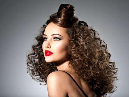 Bella donna con l'acconciatura creativa. Attraente ritratto della modella con i capelli ricci. Archivio Fotografico