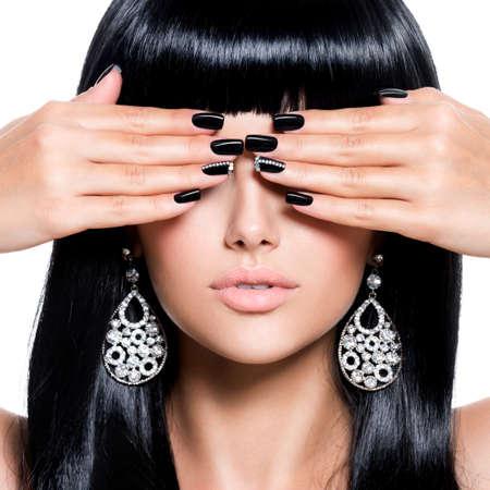 Belle femme brune aux ongles noirs. Fille avec une coiffure droite au studio Banque d'images