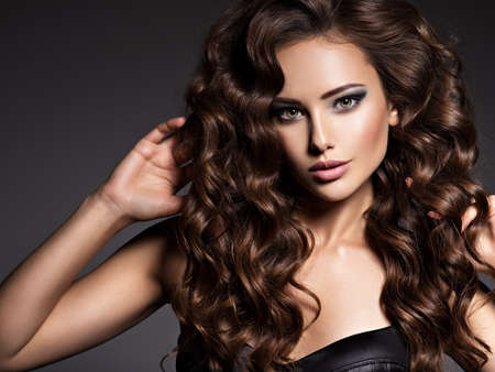 Face of the beautiful woman with long brown curly hair posing at studio over dark background Фото со стока
