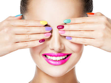 Close-up face of a woman with multicolor creative nails and pink lips. Smiling face.