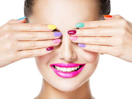Fronte del primo piano di una donna con unghie creative multicolori e labbra rosa. Faccia sorridente. Archivio Fotografico