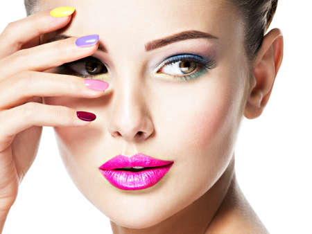 Close-up gezicht van een mooie vrouw met veelkleurige nagels en fashion make-up.