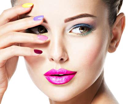 Zbliżenie twarzy pięknej kobiety z wielokolorowymi paznokciami i makijażem mody.
