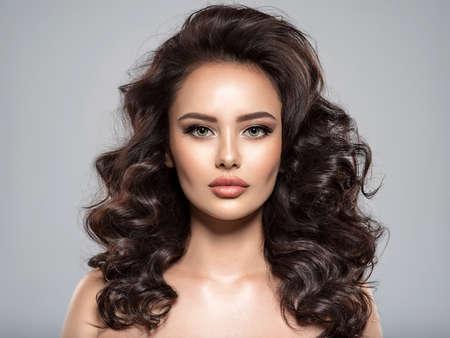 Piękna kobieta z brązowymi włosami. Piękna twarz atrakcyjnej modelki z beżowym makijażem. Portret pięknej kobiety z długimi włosami. Modelka. Piękna oszałamiająca dziewczyna z kręconą fryzurą. Zdjęcie Seryjne