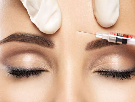 Portrait of young Caucasian woman getting botox cosmetic injection in forehead. Beautiful woman gets botox injection in her face.