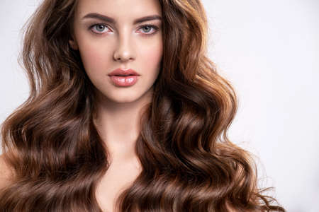 Portrait of a young beautiful woman with a long hair. Attractive fashion model with brown hair - isolated on white background. Young girl with wavy hair looks to the camera.