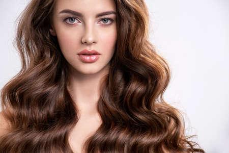 Retrato de una mujer joven y bella con un pelo largo. Modelo de moda atractivo con cabello castaño - aislado sobre fondo blanco. Chica joven con cabello ondulado mira a la cámara.