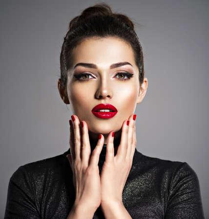 Closeup ritratto di bella donna con trucco luminoso e unghie rosse. Sexy giovane ragazza adulta con rossetto rosso.