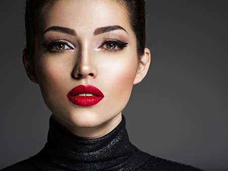 Schöne junge Modefrau mit rotem Lippenstift. Glamour-Mode-Modell mit hellem Glanz-Make-up posiert im Studio.