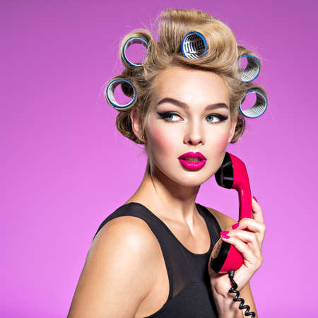 Young beautiful woman with a red vintage phone. Girl wears curlers in hair with a looking sad.