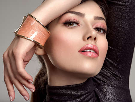 Beautiful young fashion woman with living coral lipstick. Attractive white girl wears luxury jewelry.  Glamour fashion model with bright  make-up, at studio. Stylish fashionable concept. Bracelet.