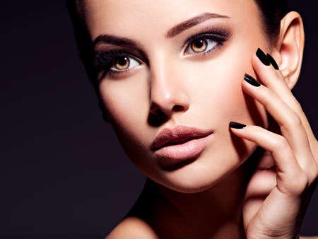 Rostro de una hermosa niña con maquillaje de moda y uñas negras posando en el estudio sobre fondo oscuro