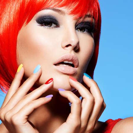 Ritratto di una modella con colore rosso brillante dei capelli e unghie multicolori. Fronte del primo piano della bella ragazza con il trucco glamour degli occhi. Foto da studio. Archivio Fotografico