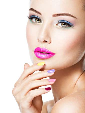 Visage en gros plan d'une belle femme avec des ongles multicolores et du maquillage de mode.