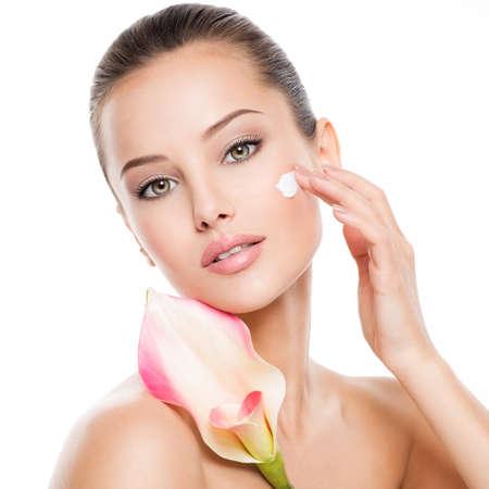 Frau, die kosmetische Creme auf einem Gesicht aufträgt. Frische Blume am Körper Standard-Bild