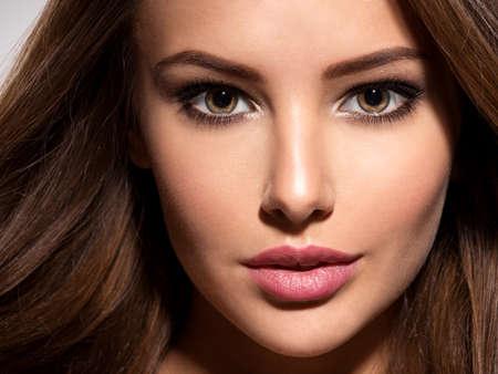 Closeup face of the beautiful woman looking at camera. Attractive girl looking at camera.