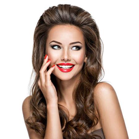 Portrait der schönen Frau mit langen Haaren wirft im Studio auf. Sexy erwachsenes Mädchen mit roten Lippen und Nägeln.