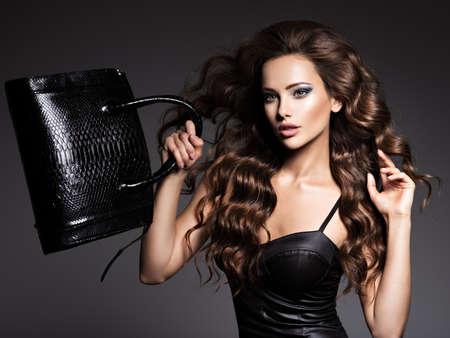 Beautiful woman with long hair in dress with black handbag posing at studio