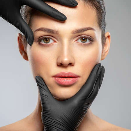Plastic surgery doctor is touching face of a patient by hands. Face skin check before plastic surgery. Beautician touching woman face. Doctor checks a skin before plastic surgery. Beauty treatments. Stock fotó