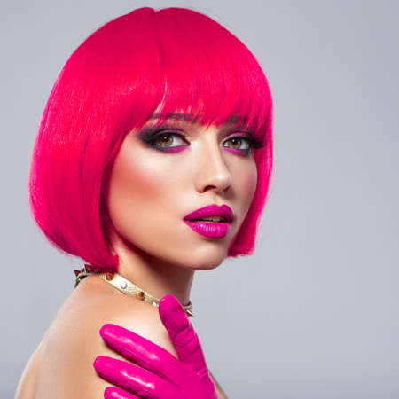 Beautiful young fashion woman with pink lipstick. Glamour fashion model with bright make-up, at studio. Closeup beauty portrait. Model with creative colored bob hairstyle. Girl in leather gloves Imagens