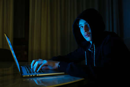 Hacker is hacking into the computer network. Young boy in a dark room with laptop. Hacker with a laptop. Computer criminal.