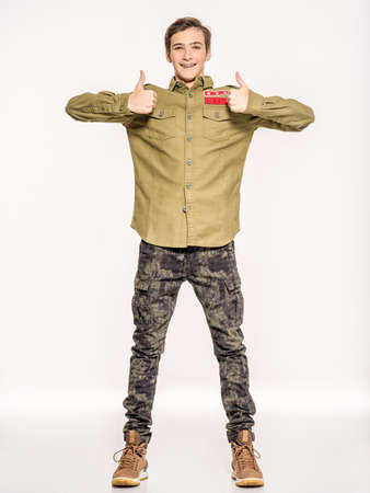 Young man in camouflage clothing shows big thumbs up. Rookie in army clothes. Teenager in khaki military clothing poses in a studio on a white background. Conscript in camouflage is showing big thumb. 스톡 콘텐츠