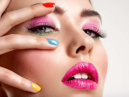 Beautiful fashion woman with a colored nails. Attractive white girl with multicolor manicure. Glamour fashion model with bright gloss make-up posing at studio. Stylish fashionable concept. Art Zdjęcie Seryjne