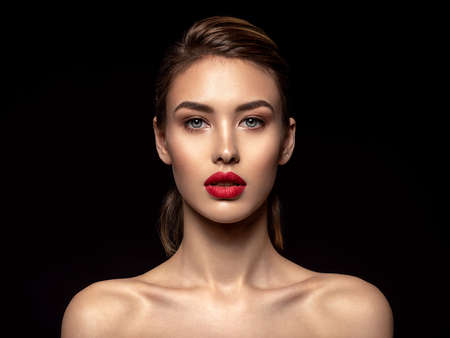 Beautiful young fashion woman with red lipstick. Glamour fashion model with bright gloss make-up  posing at studio. Closeup beauty portrait.