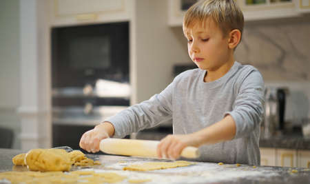 Child  rolling dough with a rolling pin, close up view. Boy rolls out the dough on the kitchen table. 8 years old boy prepares food at home. Kid rolls  a dough by rolling pin.