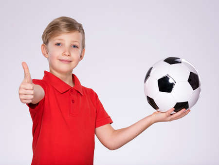 Photo of a smiling boy holding soccer ball and showing a big thumb up. posing at studio. Happy 8 years old kid in a red t-shirt with a soccer ball in hand. White child with a smile holds a soccer ball.