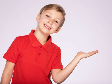 8 year old kid with a empty palm. Portrait of cheerful boy with a palm turned over up, isolated over white background. Child with an empty palm. Cheerful boy in a red t-shirt shows something Standard-Bild