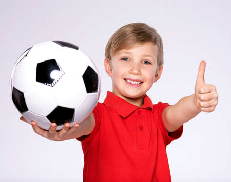 Photo of a smiling boy in sportswear holding soccer ball, posing at studio. Happy 8 years old kid in a red t-shirt with a soccer ball in hand. White child with a smile holds a soccer ball.