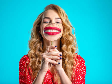Blonde holds a magnifying glass in front of her teeth. Girl with a bright smile. Funny girl. Young woman holds a magnifying glass in front of her teeth. More teeth. Dental care. Funny face of a girl