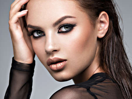 Beauty face of the young beautiful woman. Gorgeous female portrait with slicked brown hair. Young adult girl with healthy skin. Pretty model with fashion smokey eye makeup. Skin care concept. Professional makeup