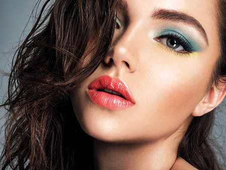 Beautiful brunette woman with bright red lipstick on her lips. Gorgeous girl with blue eye makeup. Portrait of an attractive girl with long brown hair. Fashion model. Sexy face of a pretty lady.