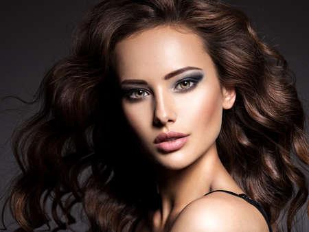 Gesicht der schönen Frau mit langen braunen Locken, die im Studio über dunklem Hintergrund posiert