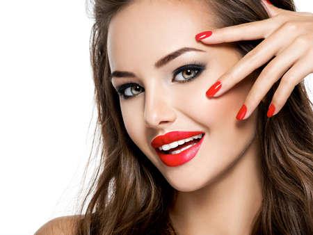 Visage de plan rapproché de belle femme de sourire avec des ongles et des lèvres rouges d'isolement sur le blanc