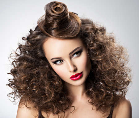 Beautiful woman with creative hairstyle. Attractive portrait of the fashion model with curly hair.