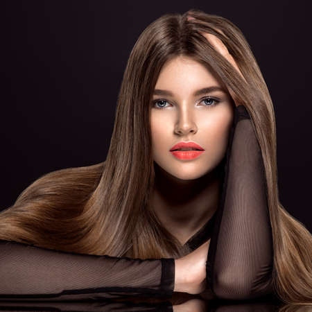 Woman with beauty long brown hair. Fashion model with long straight hair. Fashion model with a smokey makeup. Pretty woman with living coral color lipstick on lips.