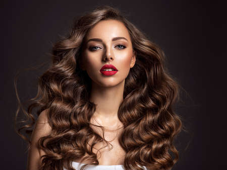 Beautiful woman with long brown hair. Beautiful face of an attractive model with red lipstick. Beauty of curly hair. Closeup portrait of caucasian stunning girl. Stockfoto