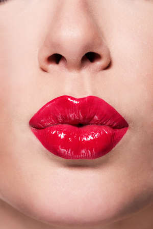 Closeup beautiful female lips with red lipstick. Glamour fashion bright gloss make-up.