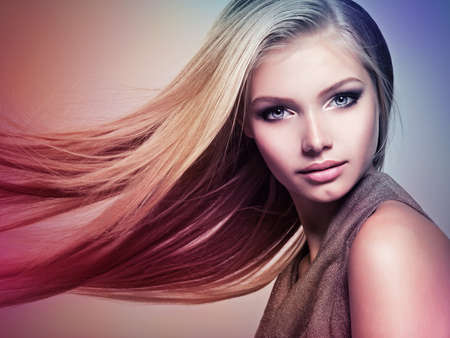 Face of the Beautiful young woman with long straight hair. Closeup portrait of a pretty girl over creative colored background