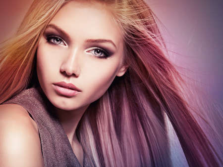 Face of the Beautiful young woman with long straight hair. Closeup portrait of a pretty girl over creative colored background Фото со стока