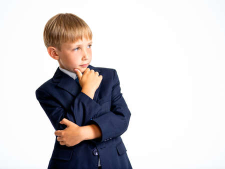 Confident blond boy dressed in a formal suit with blue tie lookinw away. Serious  kid in a blue business suit, posing at studio.  Photo of a cute little businessman boy.  Leader conception.
